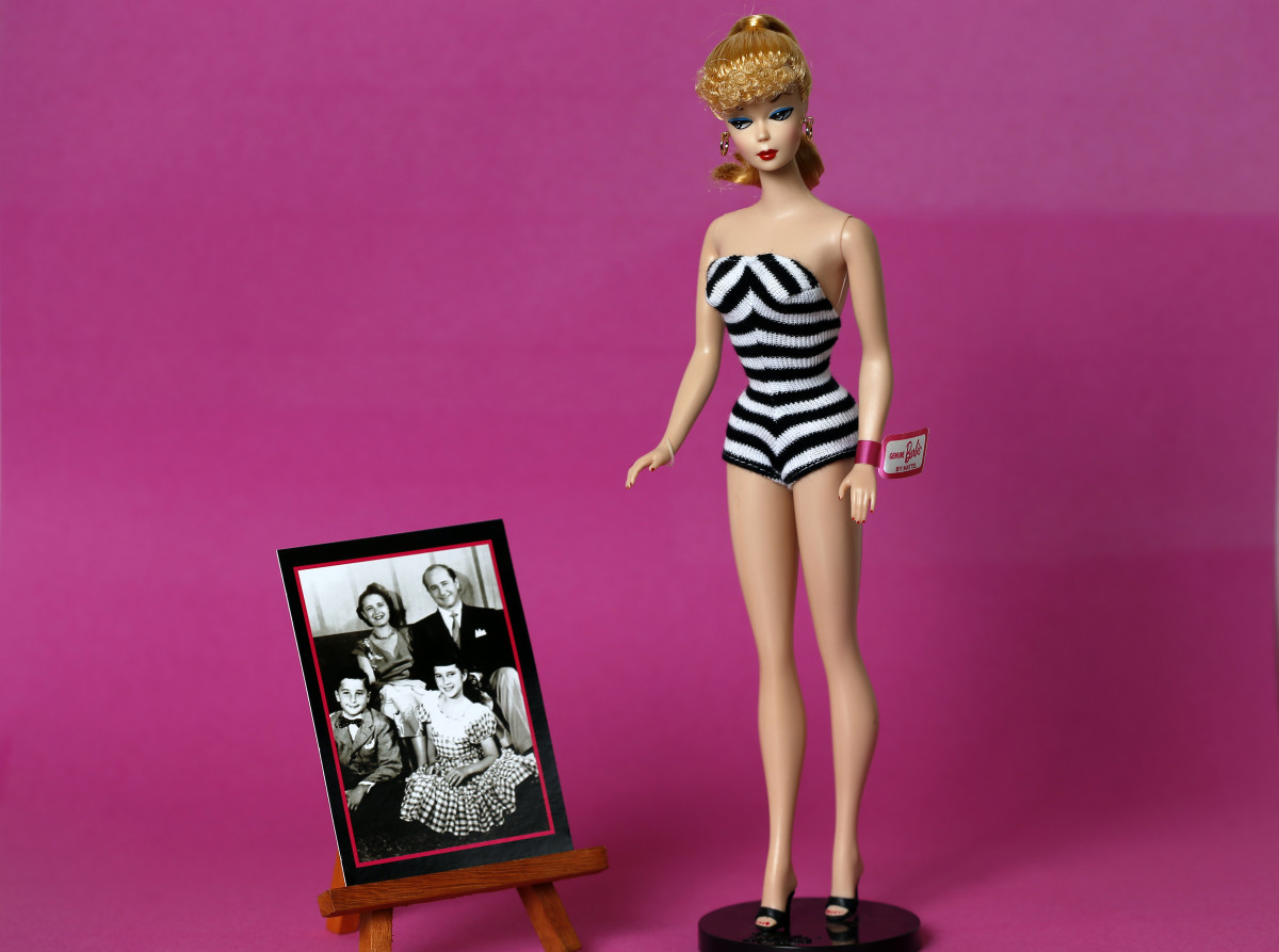 An original 1959 Barbie on display next to a photo of creator Ruther Handler's family.