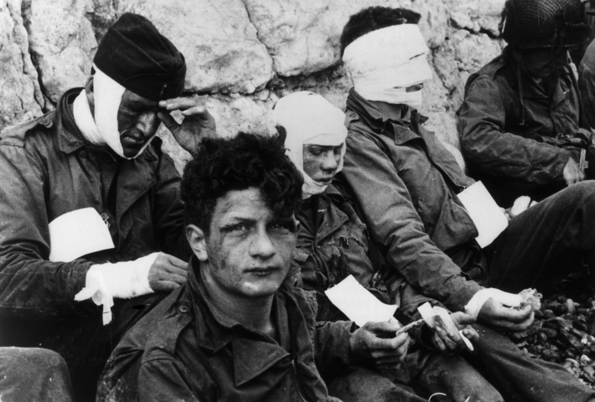 Wounded U.S. soldiers of the 3rd Battery, 16th Infantry Regiment, 1st US Infantry Division, lean against chalk cliffs while eating and smoking after storming Omaha Beach in Normandy on D-Day.