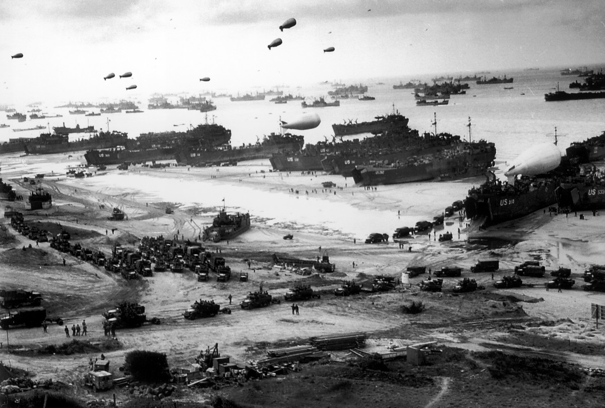 Massive landing and deployment of U.S. troops, supplies and equipment day after victorious D-Day action on Omaha Beach, barrage balloons keep watch overhead for German aircraft while scores of ships unload men and materials.