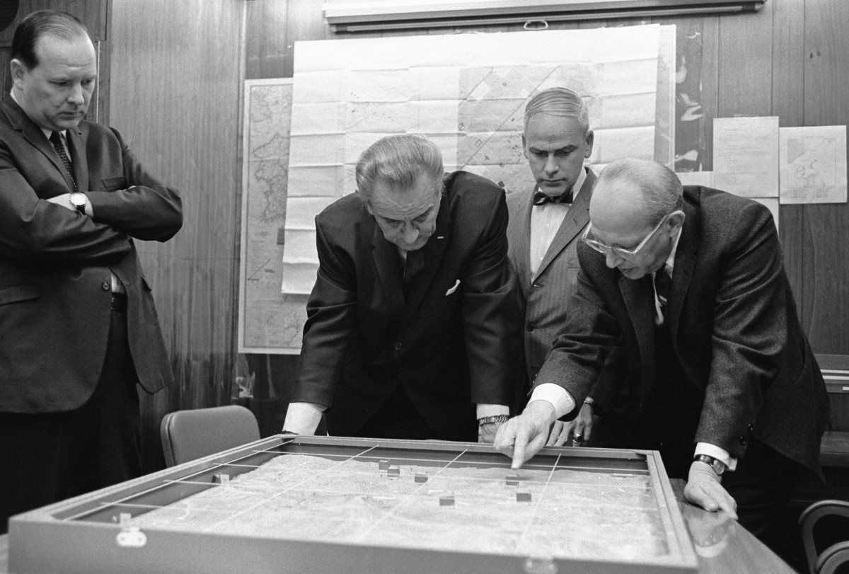 In the White House Situation Room, Walt Rostow shows President Lyndon B. Johnson options for a military attack on a site in Vietnam during the war in 1968.