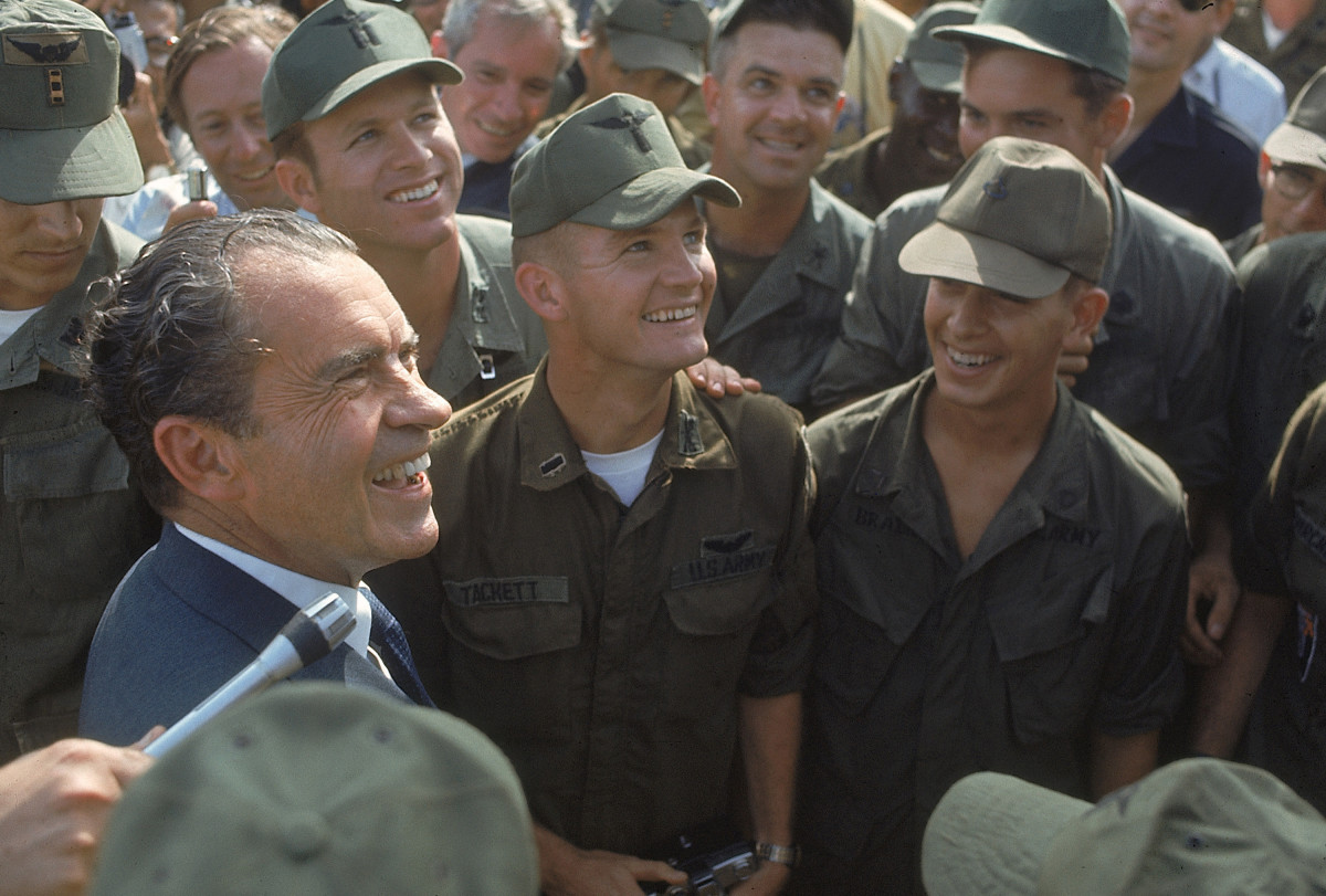 President Richard Nixon mingling with a crowd of U.S. soldiers during a surprise visit to a war zone in South Vietnam, 1969.