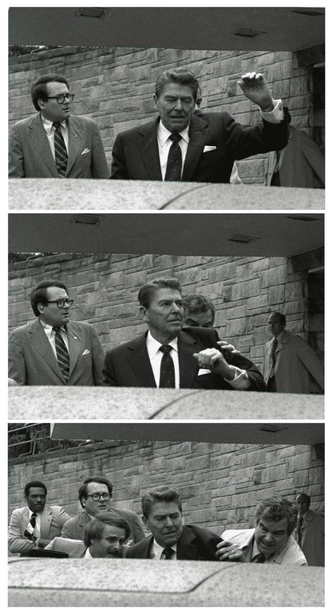 President Reagan waves, then looks up before being shoved into his limousine by Secret Service agents after being shot outside a hotel in Washington.