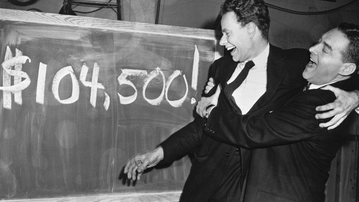 Emcee Jack Barry (right) bear hugs Charles Van Doren, Columbia instructor, after the latter won 104,500 on the TV quiz show 'Twenty-One' (Getty Images)