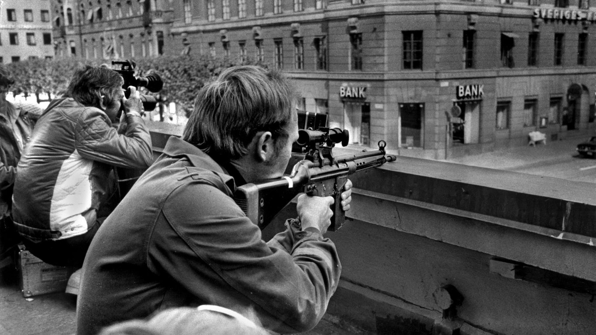 Press photographers and police snipers lie side by side on a roof opposite the bank where hostages were being held on August 24, 1973.