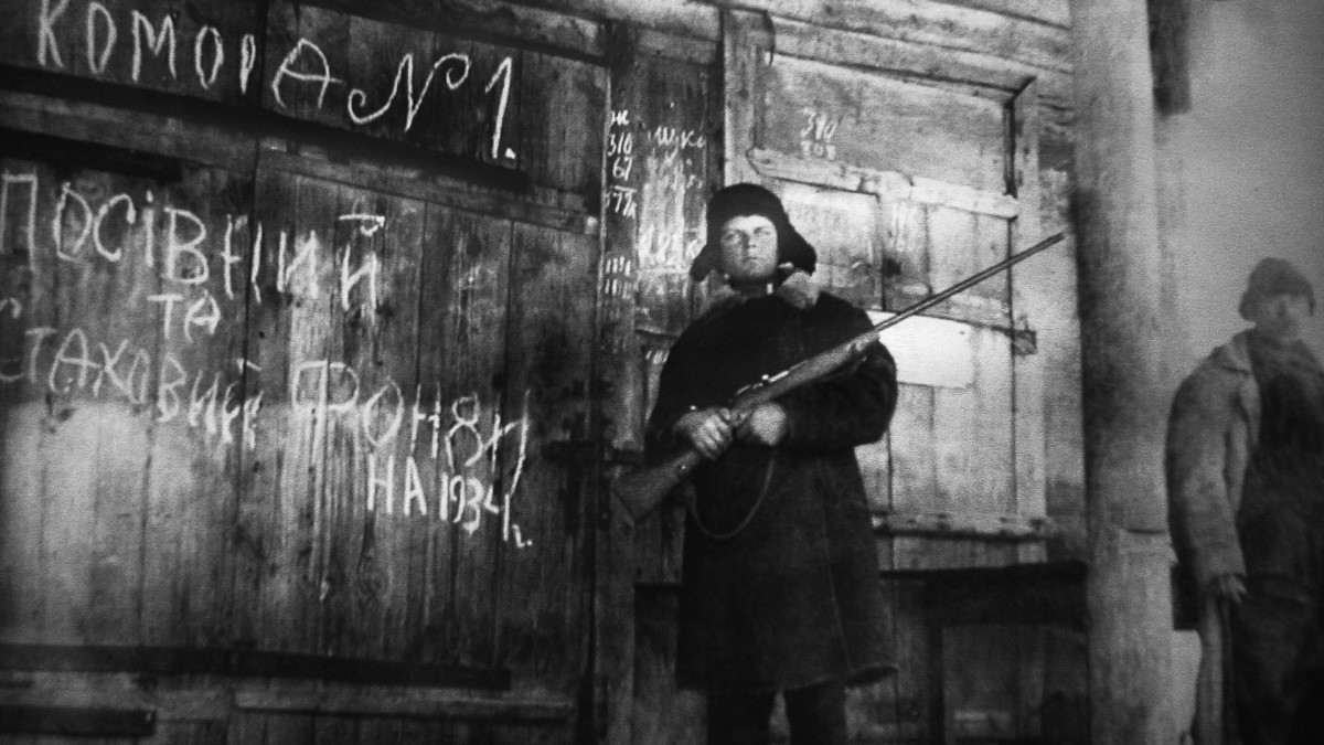 An armed man guards emergency supply grain during the Ukrainian famine of early 1930s.