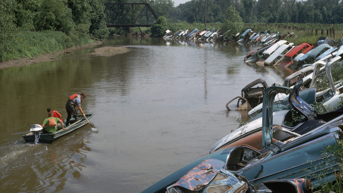 Three men in a motor boat take water samples of the Cuyahoga River where the shore is lined with semi-submerged automobile wreckage in 1968.
