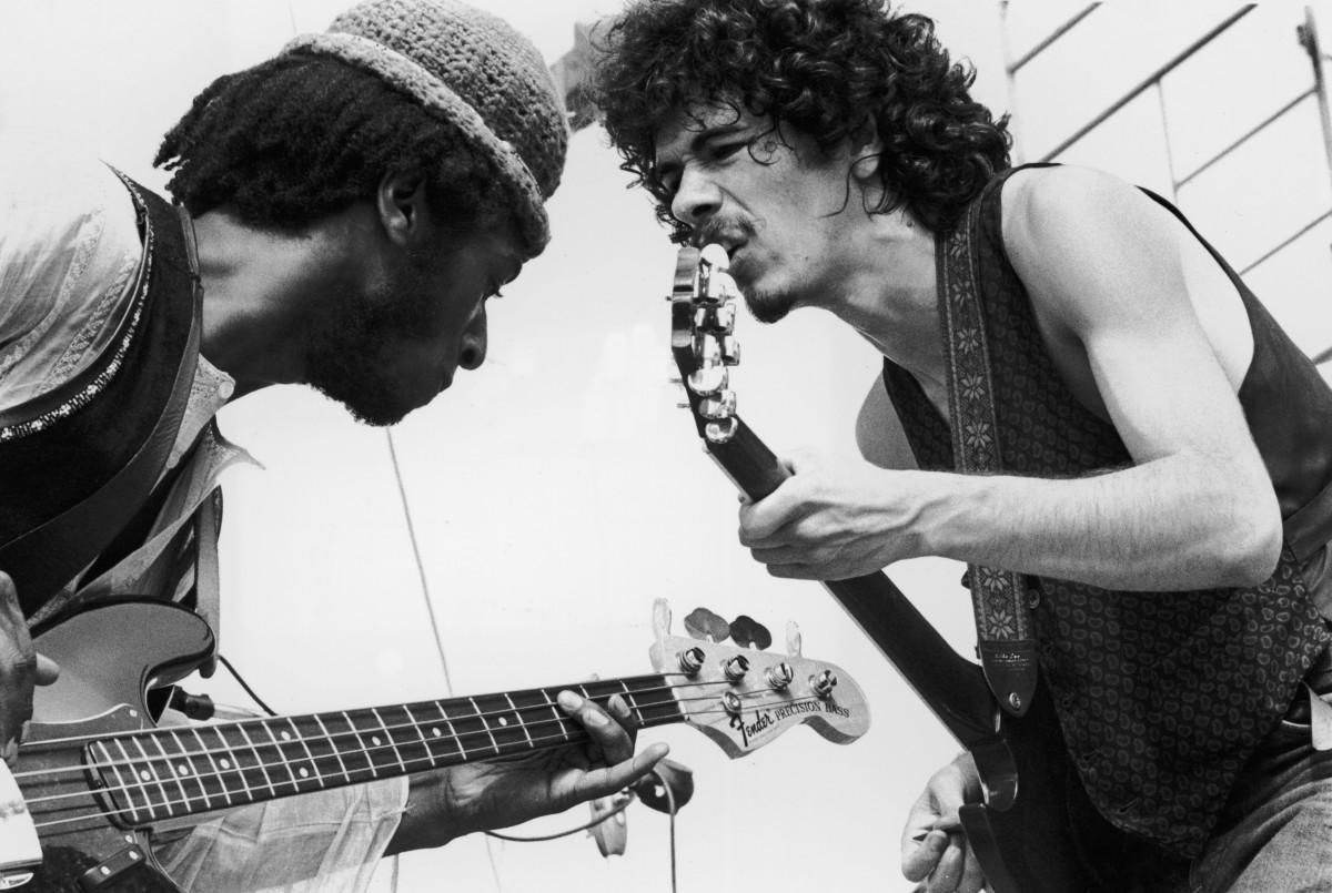 Carlos Santana (right) and bassist David Brown perform with the group Santana at the Woodstock Music Festival.