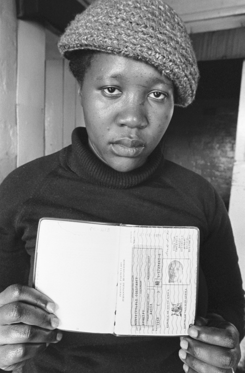 "A woman shows the ""interior passport"" that she must have to enter Cape Town during work hours, circa 1984. The rest of the time, people of color were not allowed in the cities."