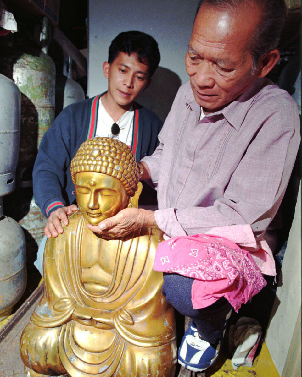 Jose Roxas, right, holds the Golden Buddha as Henry Roxas, son of Rogelio, the original owner of the buddha, watches at a courthouse in Baguio City, where it was ordered released to the trusteehip of the Roxas family on Monday June 24, 1996.
