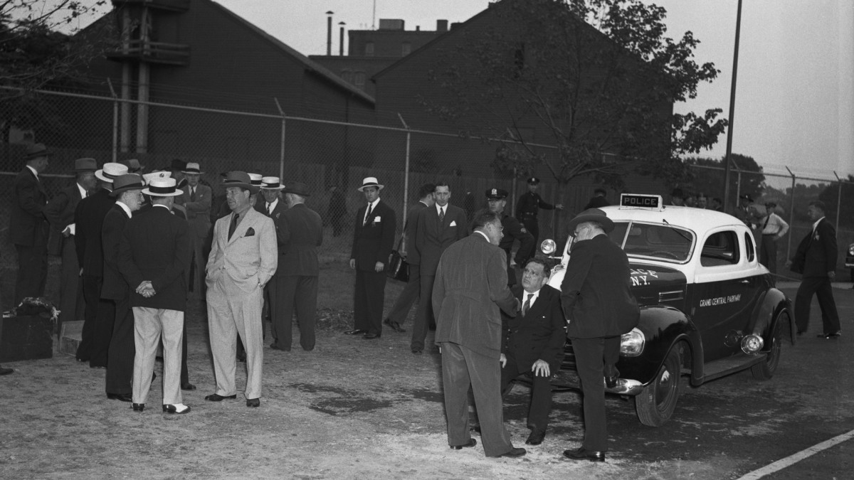 New York's Mayor, seated on the bumper of the police car, at the scene of the bomb explosion, speaking with detectives as fragments and clues are investigated on site.