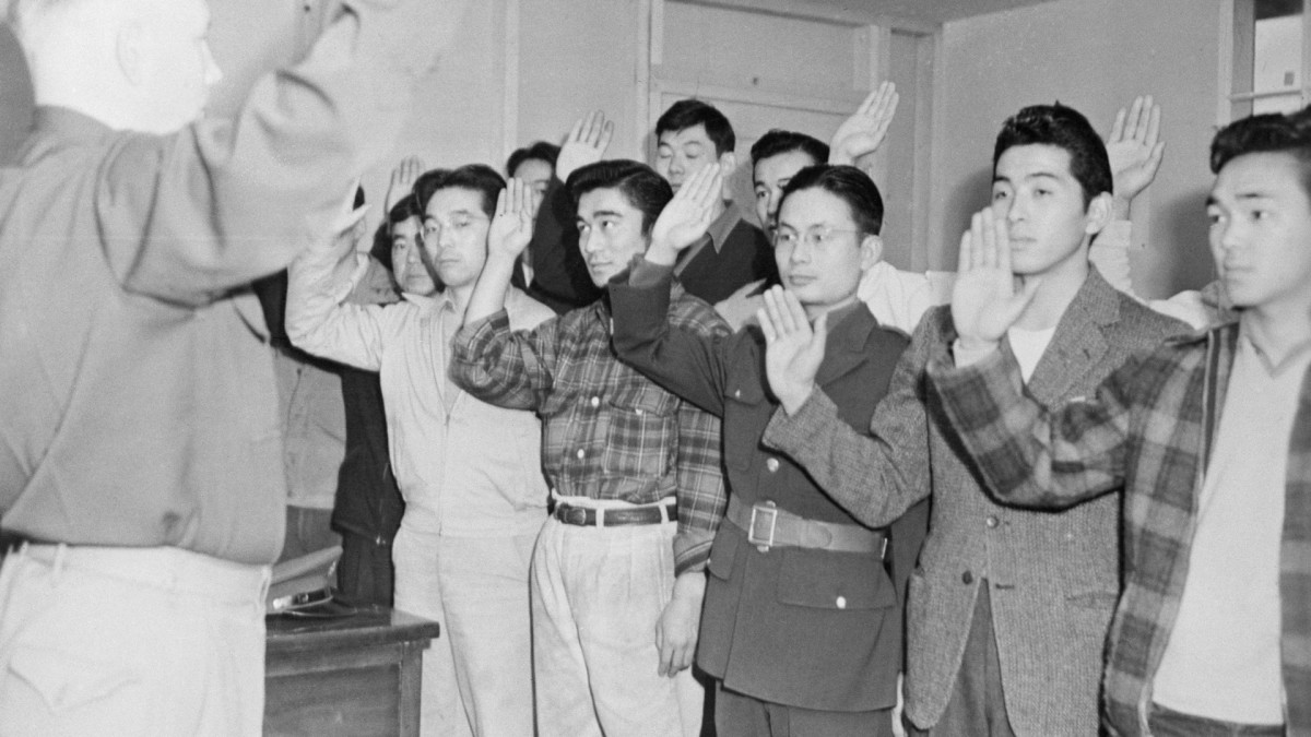 Captain Jerry Tobin, infantry recruiting officer, shown swearing in a batch of Nisei youths about to undergo examinations of their ability as interpreters, in written and spoken Japanese, recruited for service in the US Army.