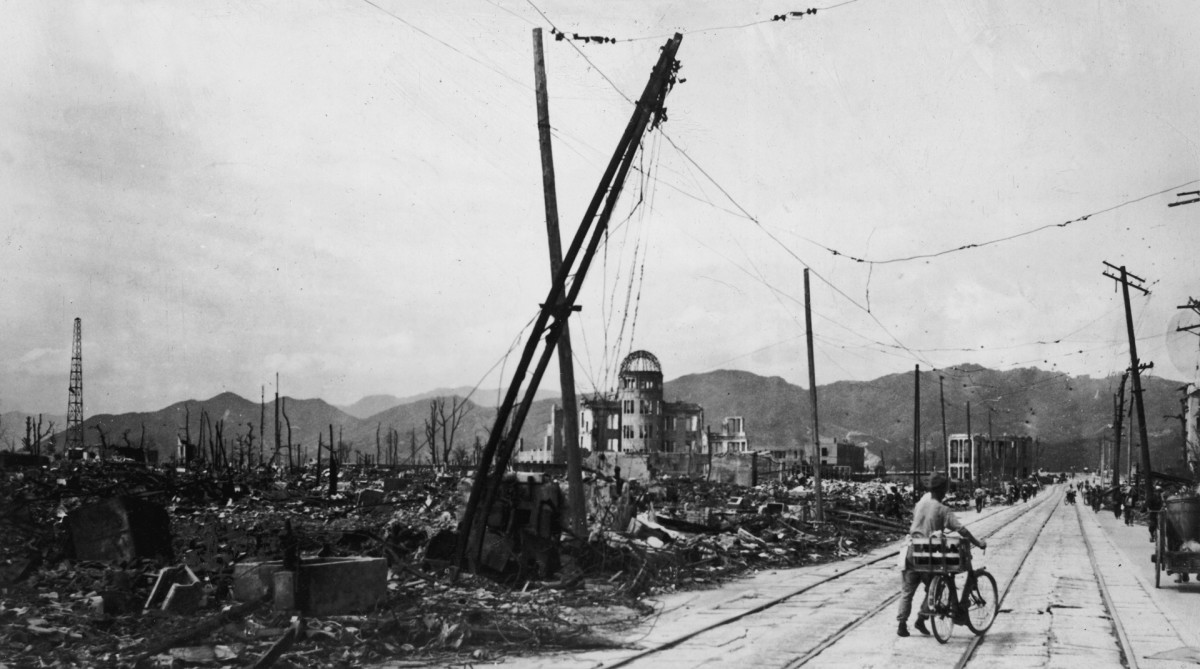 A man wheels his bicycle thorough Hiroshima, days after the city was leveled by an atomic bomb blast, Japan. The view here is looking west-northwest, about 550 feet from where the bomb landed, known as X, on August 6, 1945.