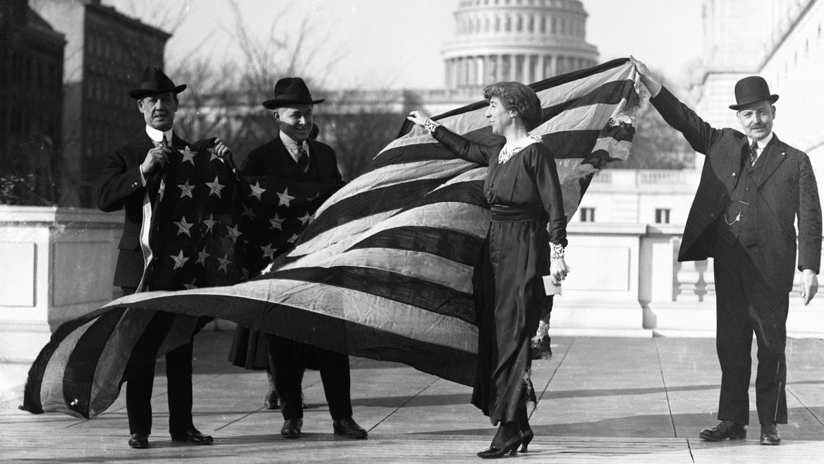 Congresswoman Jeannette Rankin is presented with the flag that flew at the House of Representatives during the passage of the suffrage amendment, 1918.