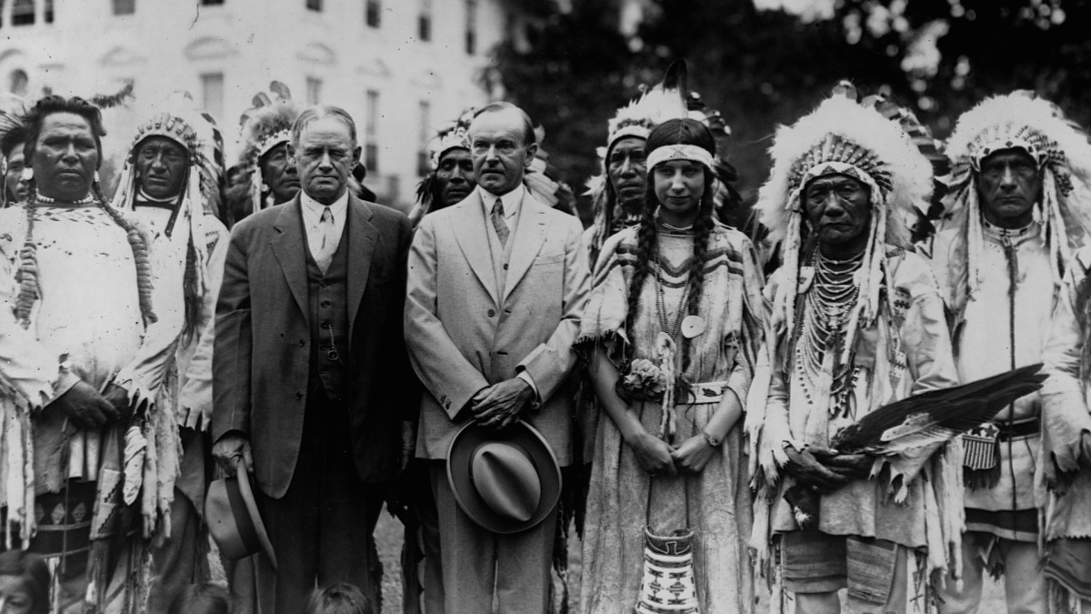 President Calvin Coolidge standing with Charles H. Burke, Commissioner of Indian Affairs, and members of the Blackfoot tribe, 1927.