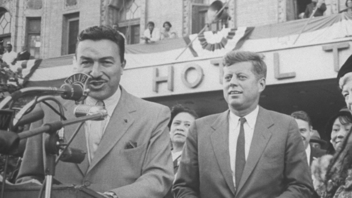 Democratic Representative Adam Clayton Powell is shown introducing Democratic Party presidential candidate John Kennedy in front of the Hotel Theresa in Harlem during his campaign tour.