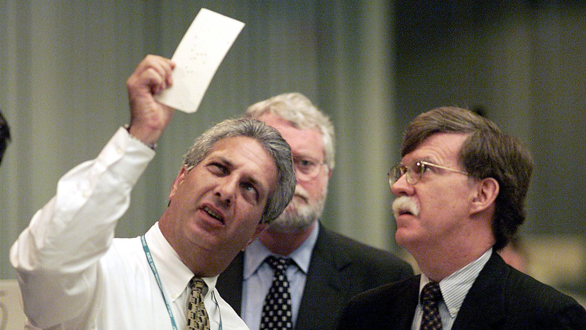 Palm Beach canvassing board member Judge Charles Burton (L) takes a close look at a questionable ballot with Republican attorney John Bolton (R) and democratic attorney Gerry McDonough (C) at the Palm Beach county Emergency Operations Center in West Palm Beach, Florida, on November 18, 2000.