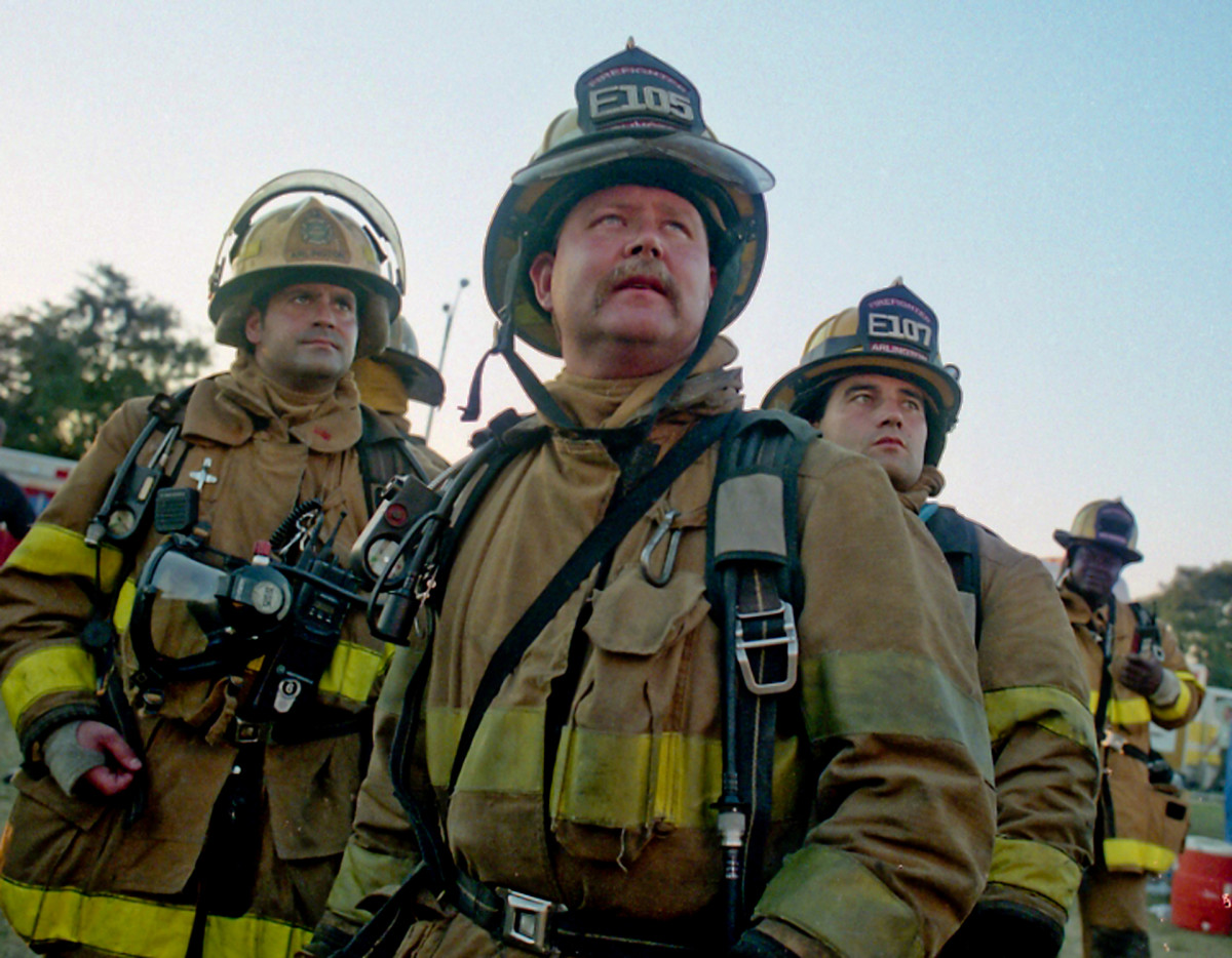 Firefighters from Arlington County, Virginia look up at the Pentagon before they enter as flames reappear from the upper floors on September 11, 2001.