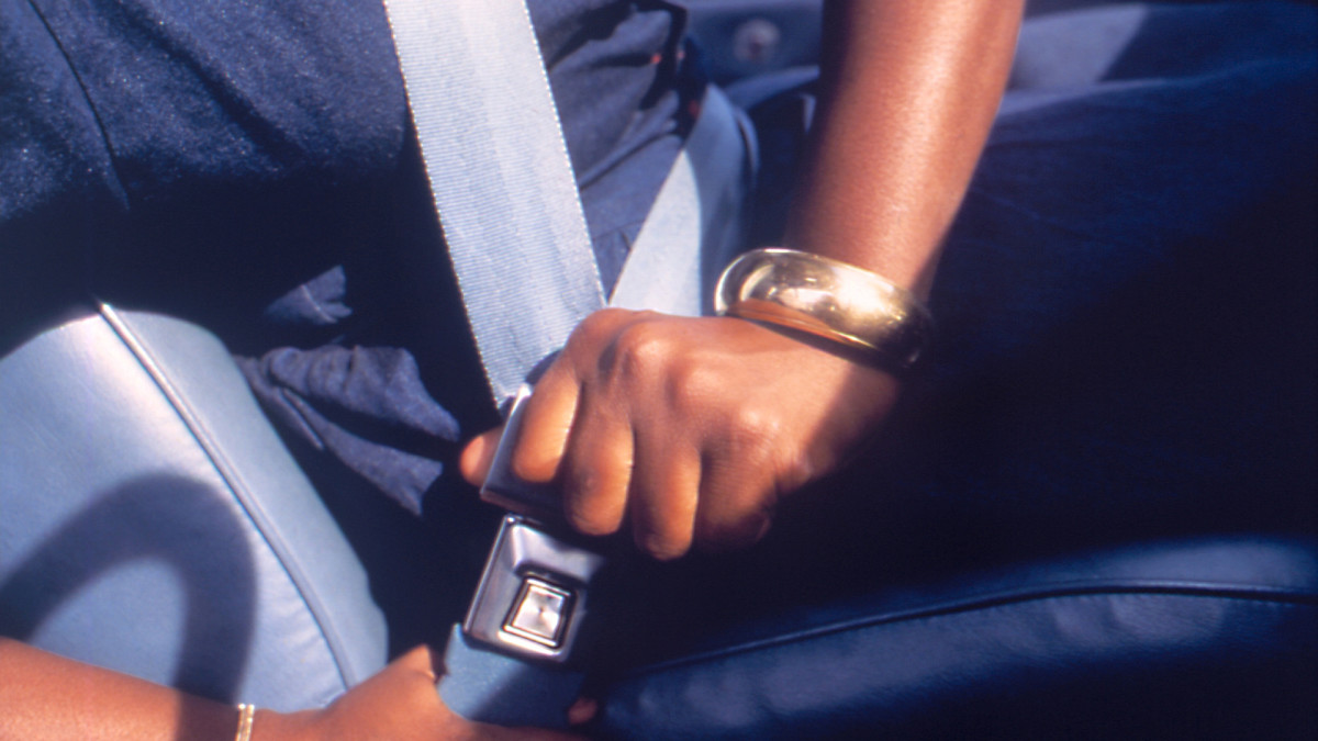 A person fastening her seat belt in a motor vehicle; image courtesy of the CDC, 1990.