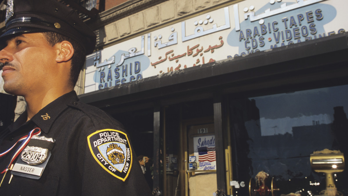 NYPD officer guarding stores of the Arab community to protect against displaced hostility in the wake of 9/11