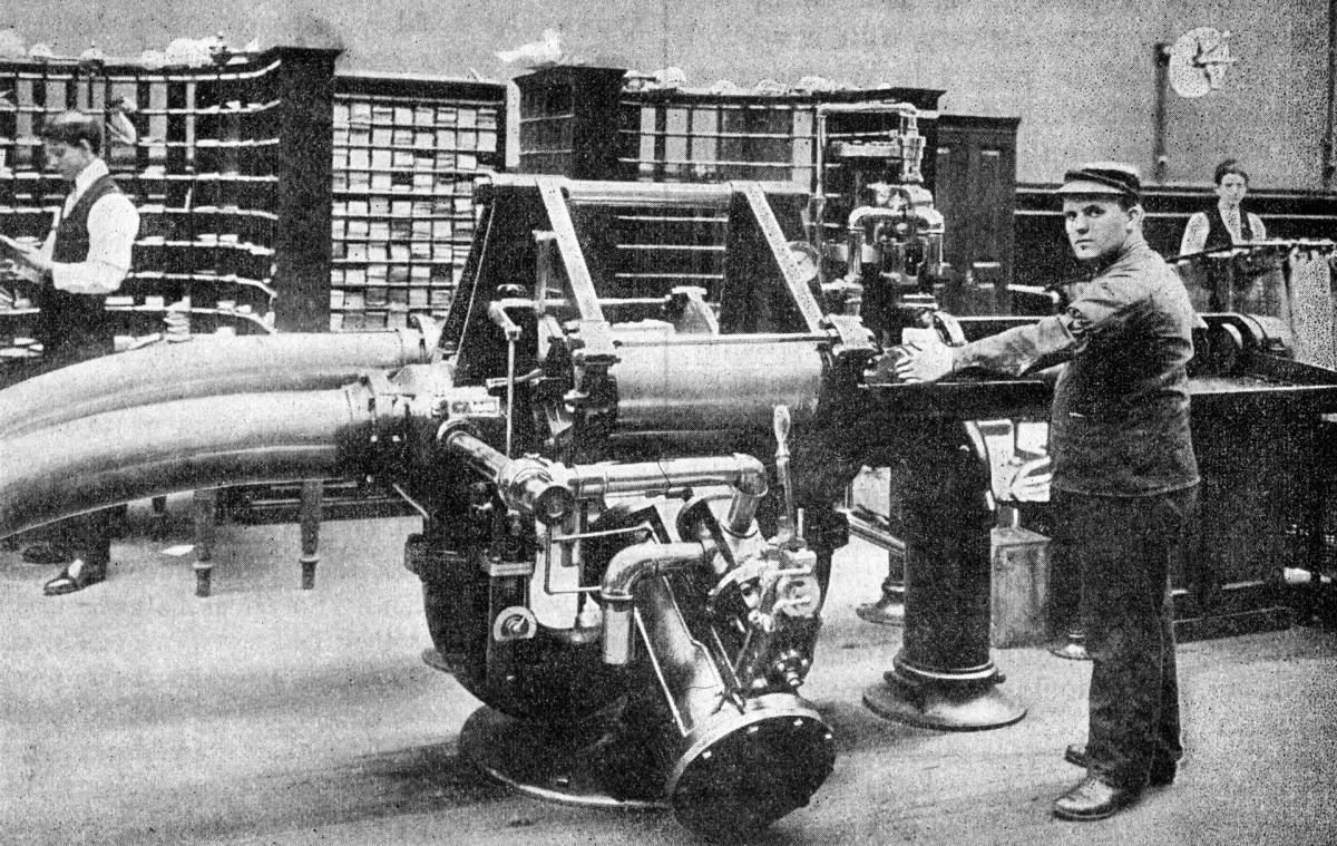 An operator preparing to feed a carrier holding about 500 letters into the transmitter for despatch through the tube from Brooklyn Post Office to New York General Post Office, a distance of about 1.75 miles, circa 1899.