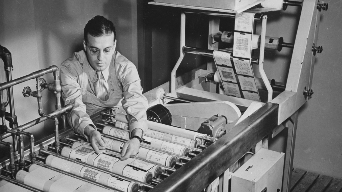 A man operates a continuous paper processing machine to develop, fix, wash and dry paper reproductions of microfilmed v-mails at the Pentagon in Washington, D.C., February 1943.