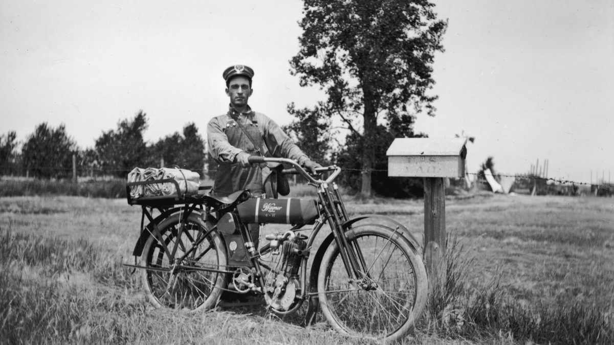 A rural postal mail carrier stands with his Wagner 4-11 motorcycle next to a postal box on his route near Newell, South Dakota, circa 1915.