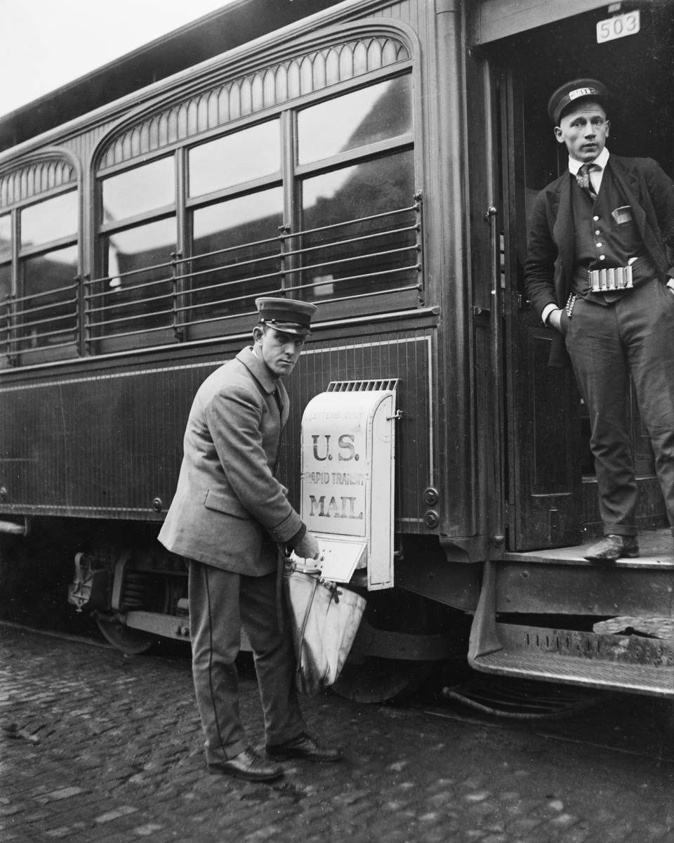 A mailman collects letters from a train mailbox, circa 1921.