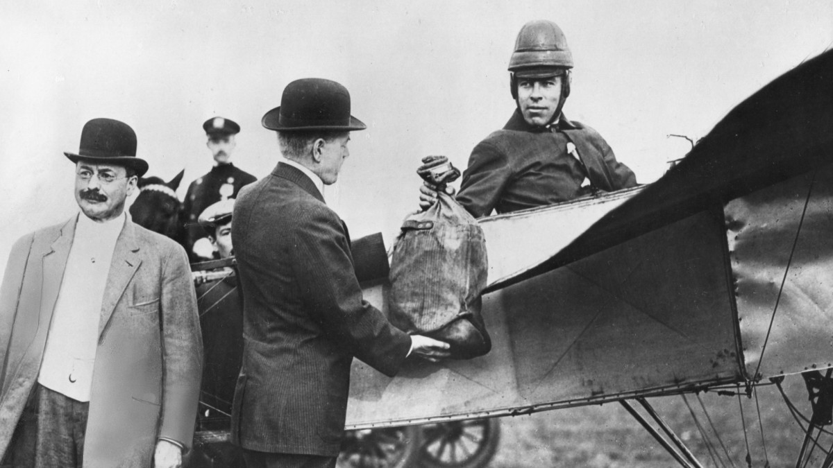 Earle Ovington, pioneer aviator, flew the first air mail in the United States in 1911. U.S. Postmaster General Frank Hitchcock participated in the historic ceremony at Sheepshead Bay, New York when he delivered the first bag of mail to Ovington.