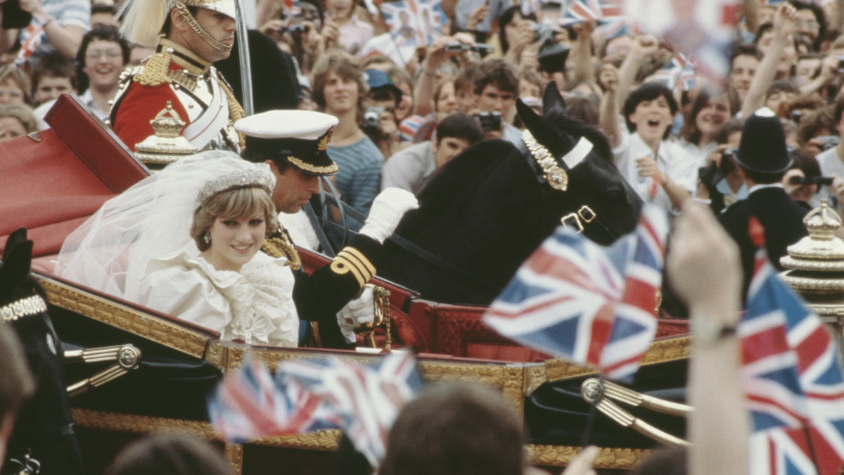 Charles, Prince of Wales, and his wife, Princess Diana, wave to the crowds following their wedding ceremony at St Paul's Cathedral.