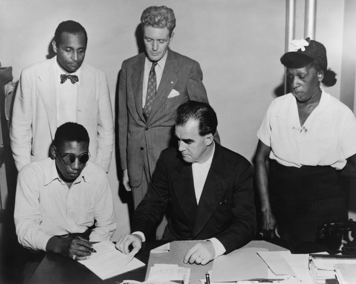 African American veteran Isaac Woodard, seated far left, was blinded by Batesburg, South Carolina police. Feb. 12, 1946. NAACP staff is assisting him in preparing his disability claim to the Veterans administration.