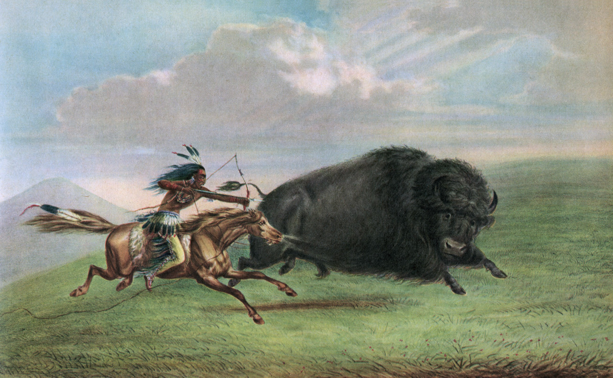 Print of a buffalo hunt, after a painting by George Catlin, depicting a Plains warrior on horseback hunting a bison in the American West, c. 1920.