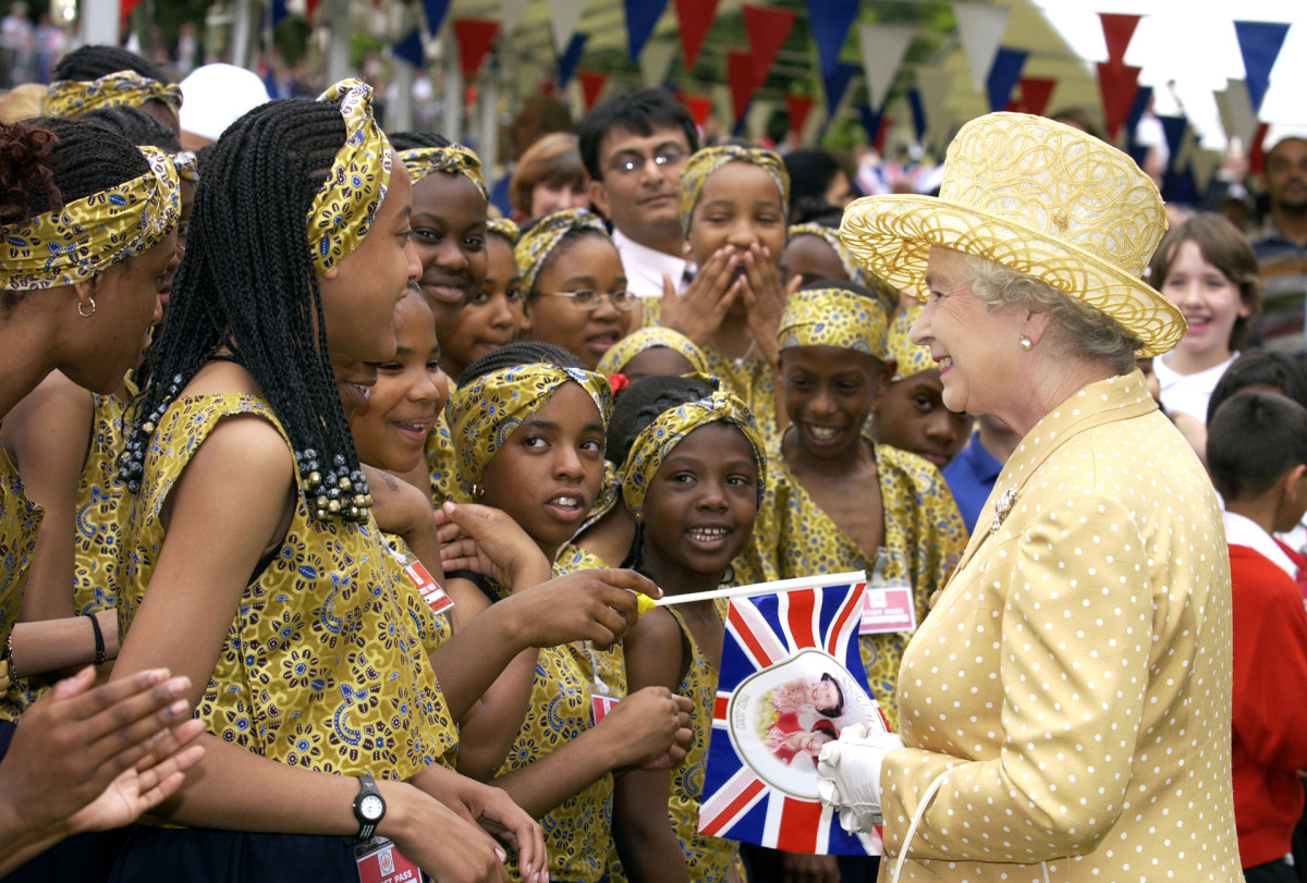 Queen Elizabeth II visiting a community picnic where locals provided musical and dance entertainment to celebrate the ethnic diversity of West London at Gunnersbury Park, June 24, 2002.