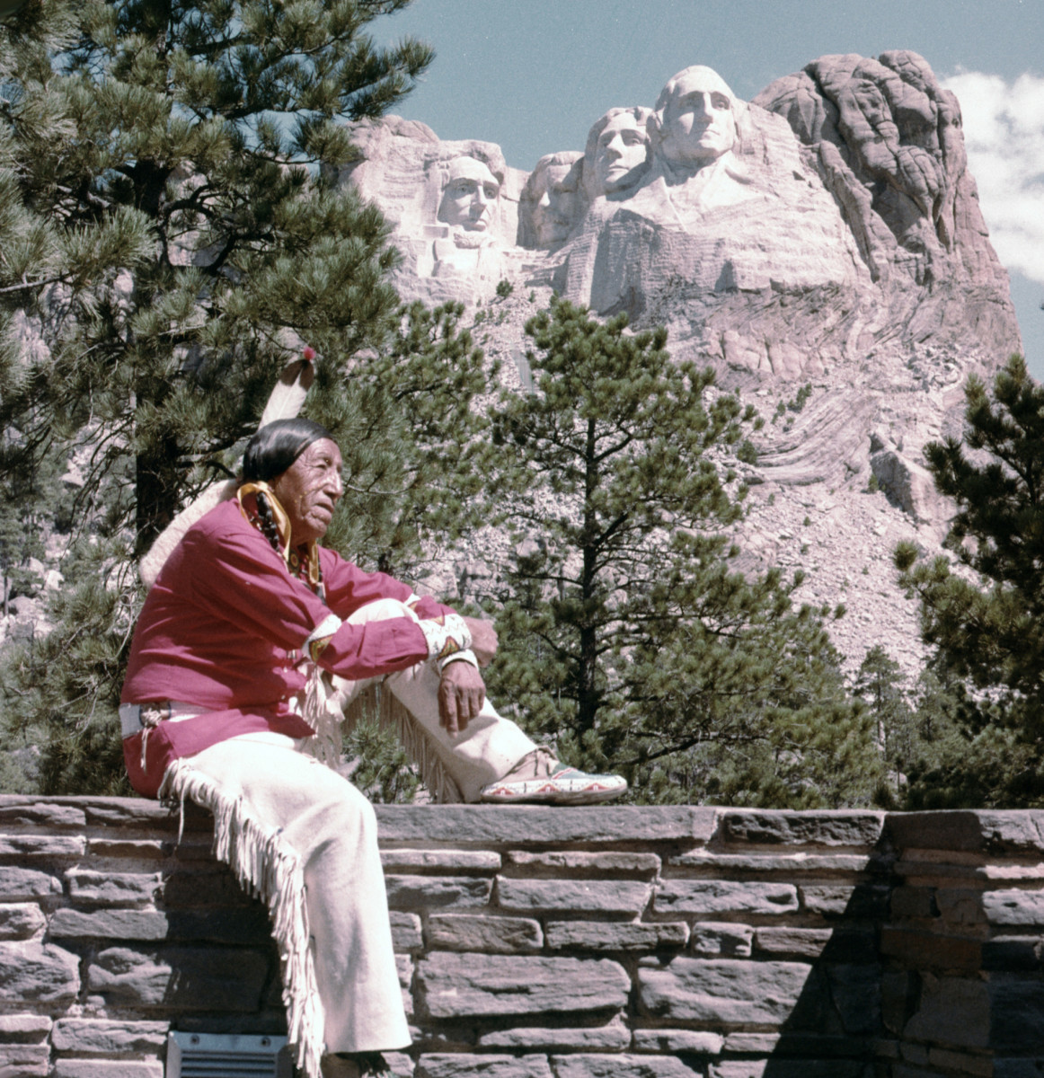 Oglala Indian Chief, Ben Black Elk, photographed in front of Mount Rushmore, c. 1962.