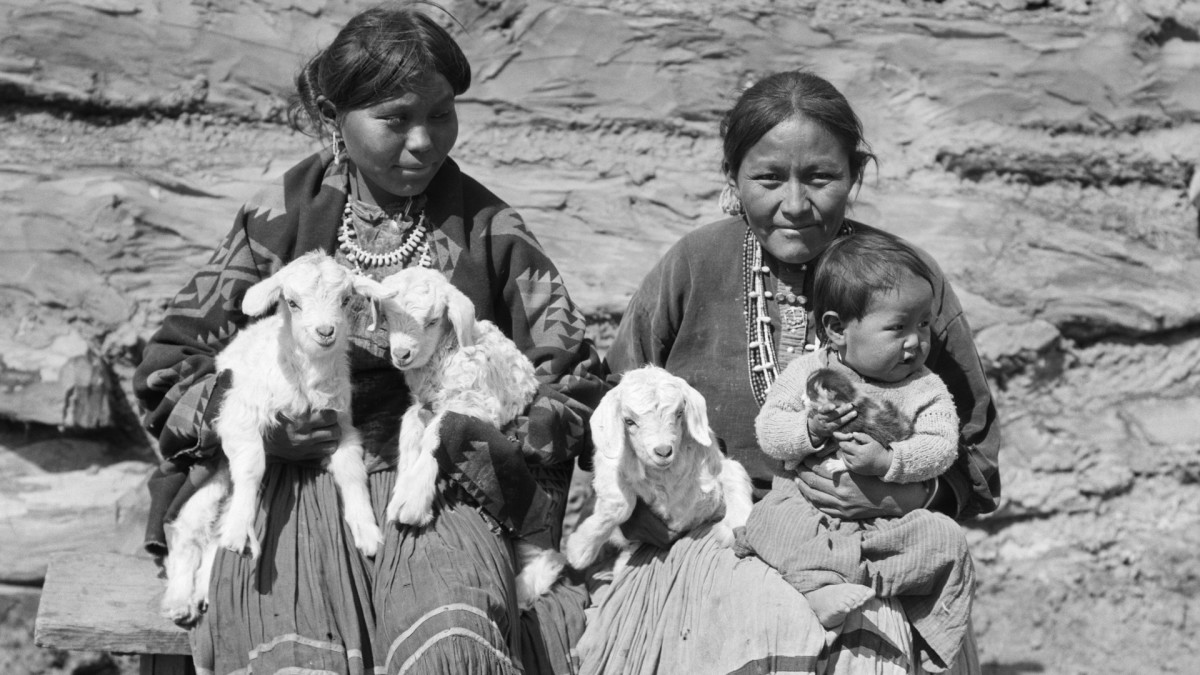 Two Navajo women, pictured with a baby and three small lambs, c. 1930s.