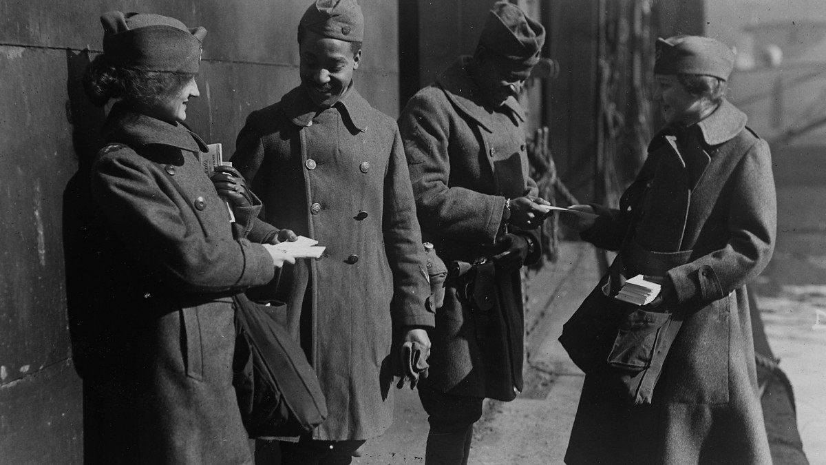Two soldiers of the 351st Field Artillery which returned on the 'Louisville' receive candy from the Salvation Army women that welcome every troopship arriving in port, 1919.