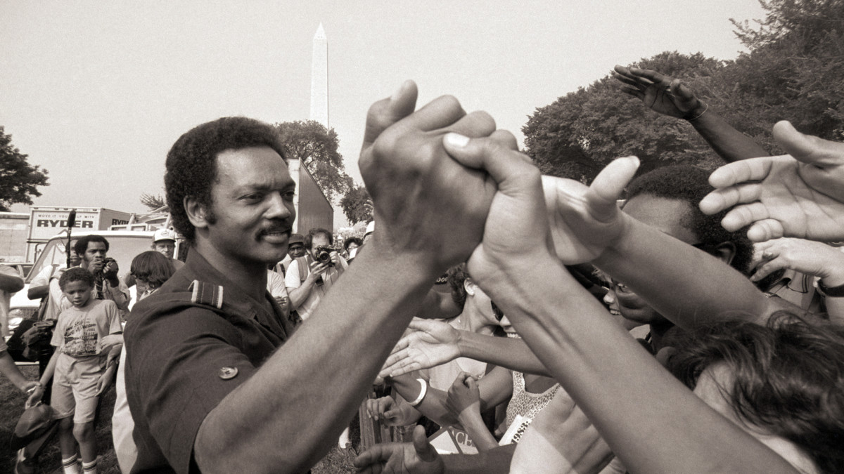 """Rev. Jesse Jackson shakes hands at the 20th anniversary commemoration of the Martin Luther King, Jr.'s Freedom March, also known as the """"March on Washington,"""" during his run for president in August, 1983."""