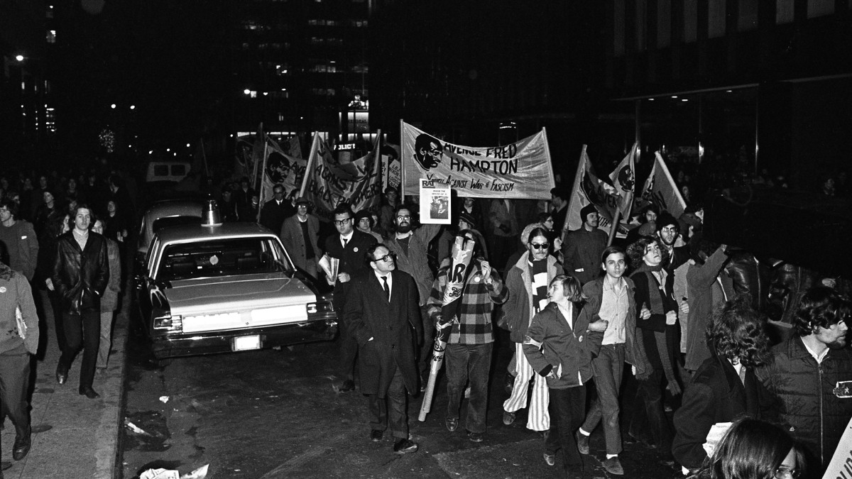 View of protestors, many with signs reading 'Avenge Fred Hampton,' a reference to the Black Panther member assassinated five days earlier by members of the Chicago Police Force, at an anti-Nixon demonstration in New York City, December 9, 1969.