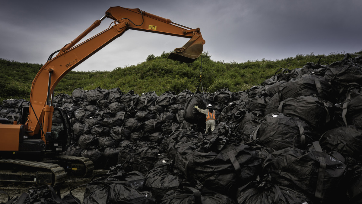 Radioactive soil has been decontaminated from the land around Fukushima and packed in black bags that are stacked on piles while waiting to be transported to the intermediate storage.