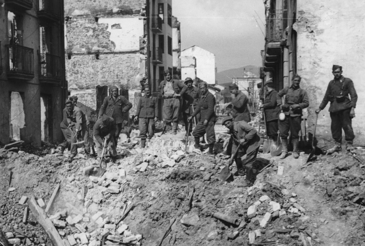 Spanish Nationalist soldiers stand atop the rubble of the town of Guernica, destroyed by German aircraft during the Spanish Civil War, May 1937