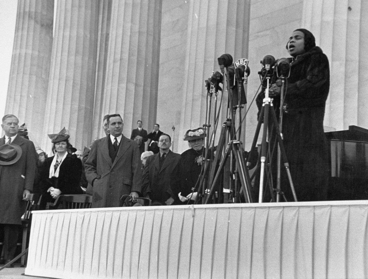 Marian Anderson gives a concert on the steps of the Lincoln Memorial as Secy. of the Interior Harold L. Ickes (L) and others listen.