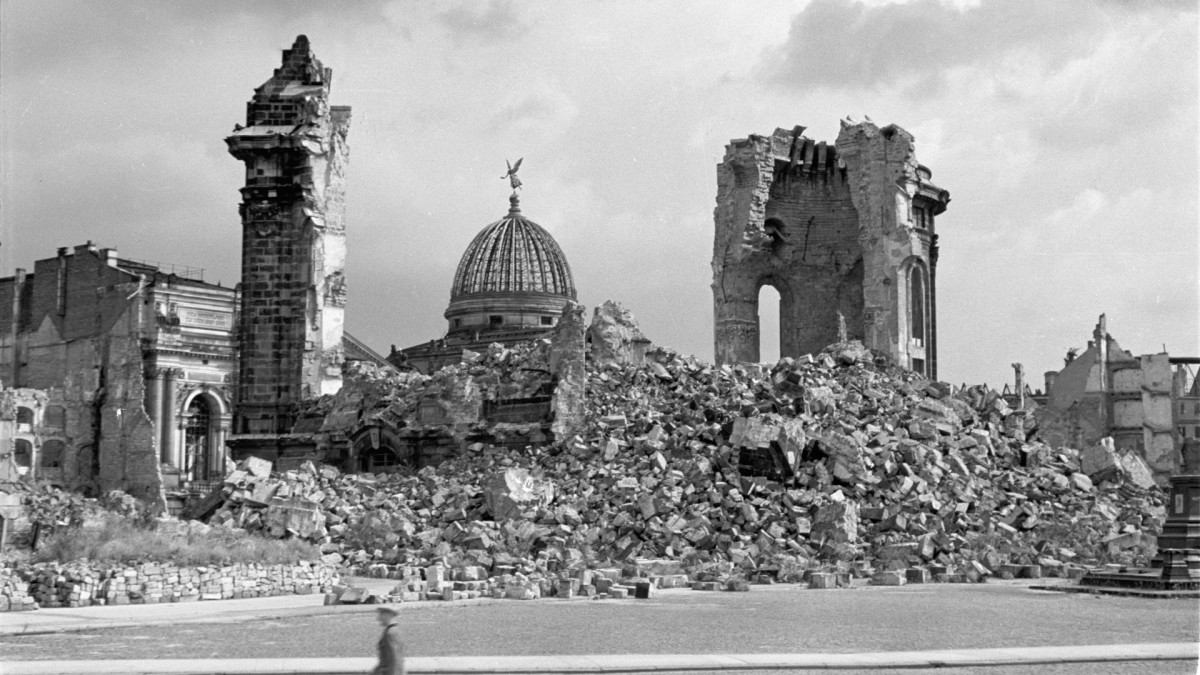 The ruins of Dresden Frauenkirche, a Lutheran church. In the background is the dome of the Dresden Academy of Fine Arts.