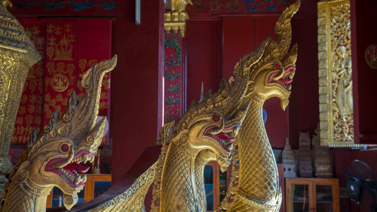 The Chariot Hall or Royal Funerary Chariot Hall at the Wat Xieng Thong in the UNESCO world heritage town of Luang Prabang in Central Laos contains King Sisavang Vong's gilded, carved wooden funeral carriage, decorated with large Naga snakes at the front.