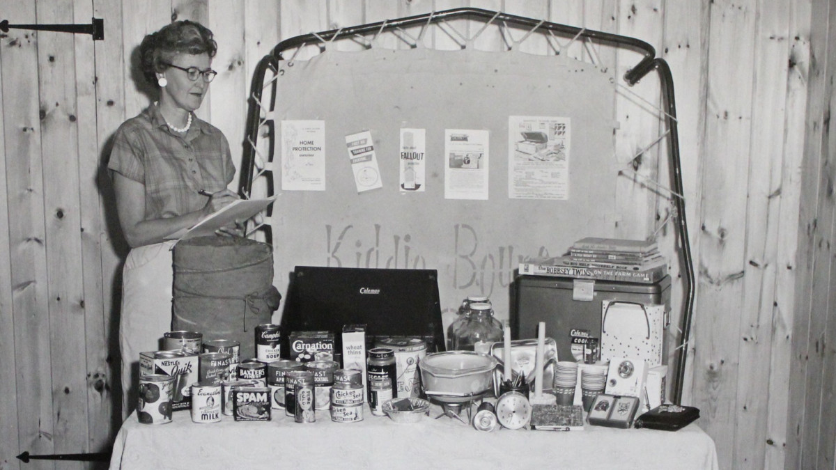 A woman as she takes an inventory of supplies for her household's fallout shelter.