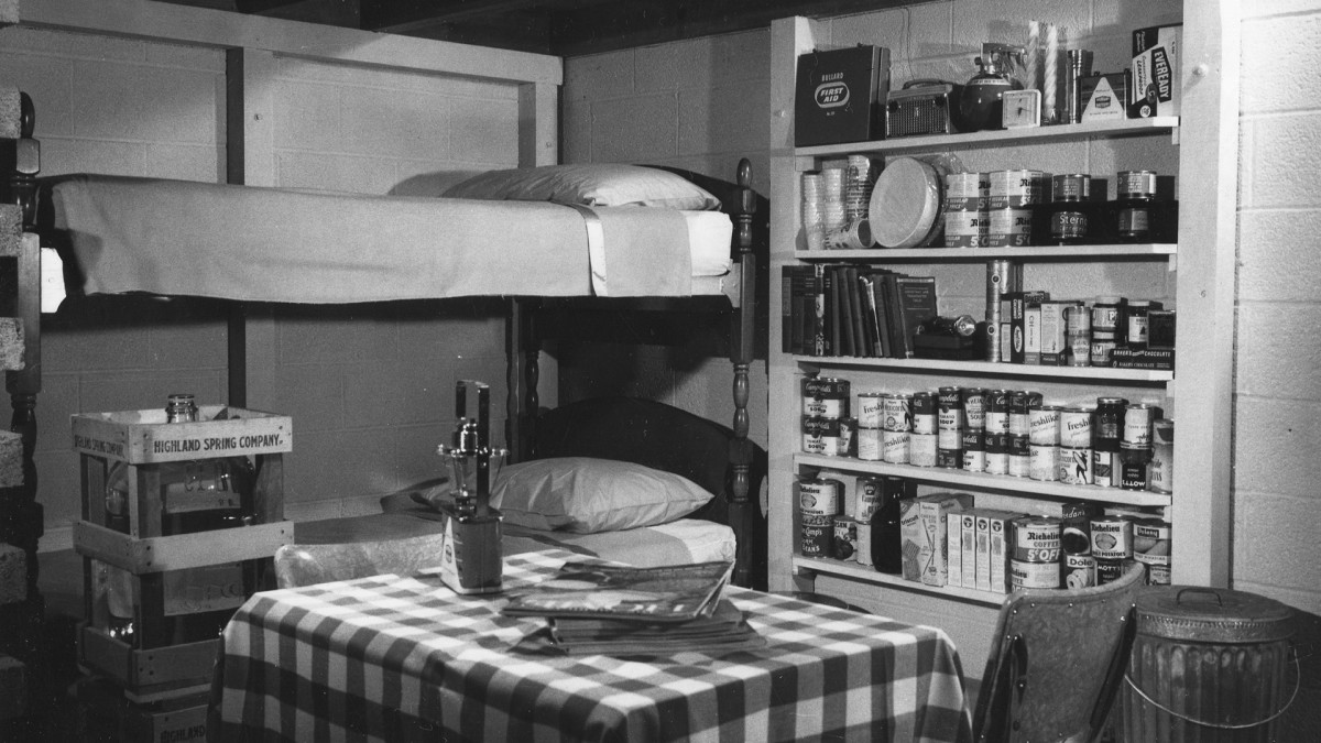 Interior view of a family's fallout shelter from the 1960s. Among the supplies are a 14-day supply of water and canned food, a battery-operated radio, auxiliary light sources and first aid supplies.