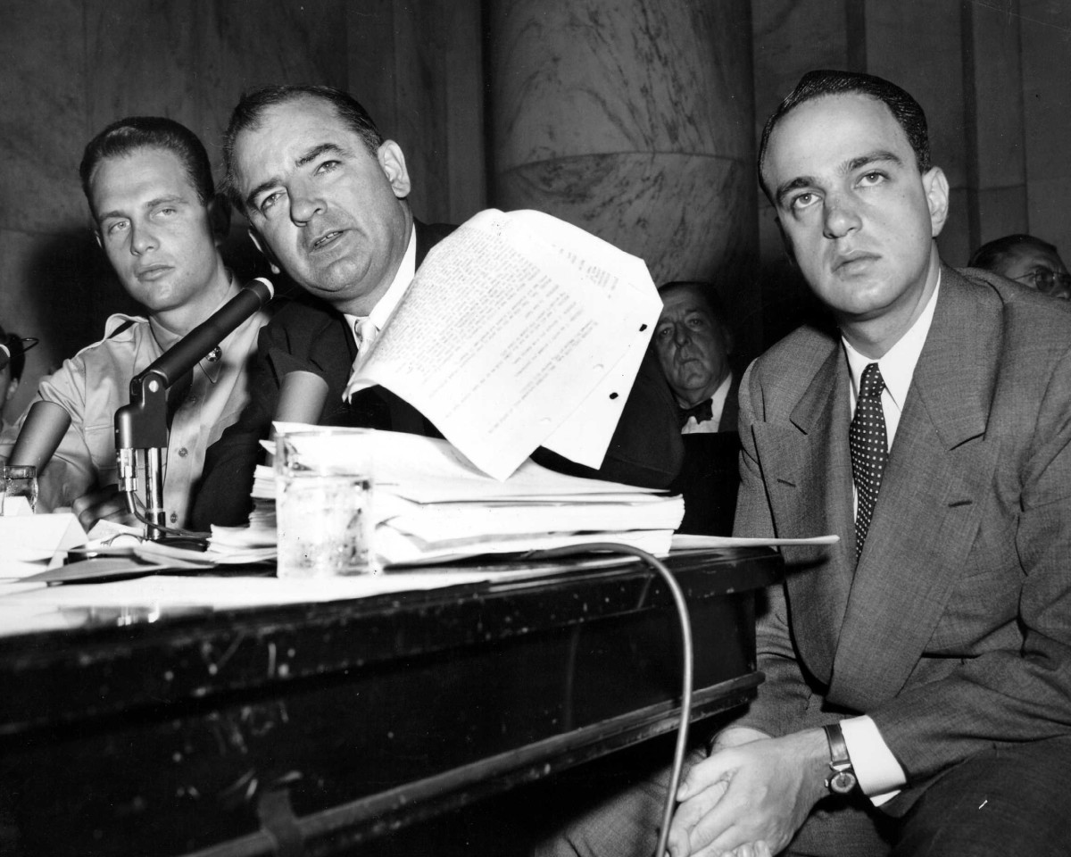 Sen. Joseph McCarthy (center) seated beside Roy Cohn (right), chief counsel to McCarthy's investigative subcommittee.
