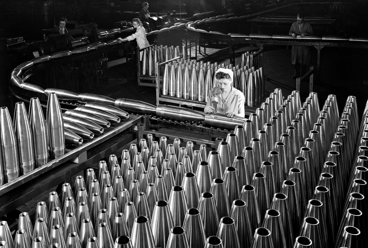 A worker inspects shell cases at the converted plant of GM's now-defunct Fisher division, known for building auto bodies.