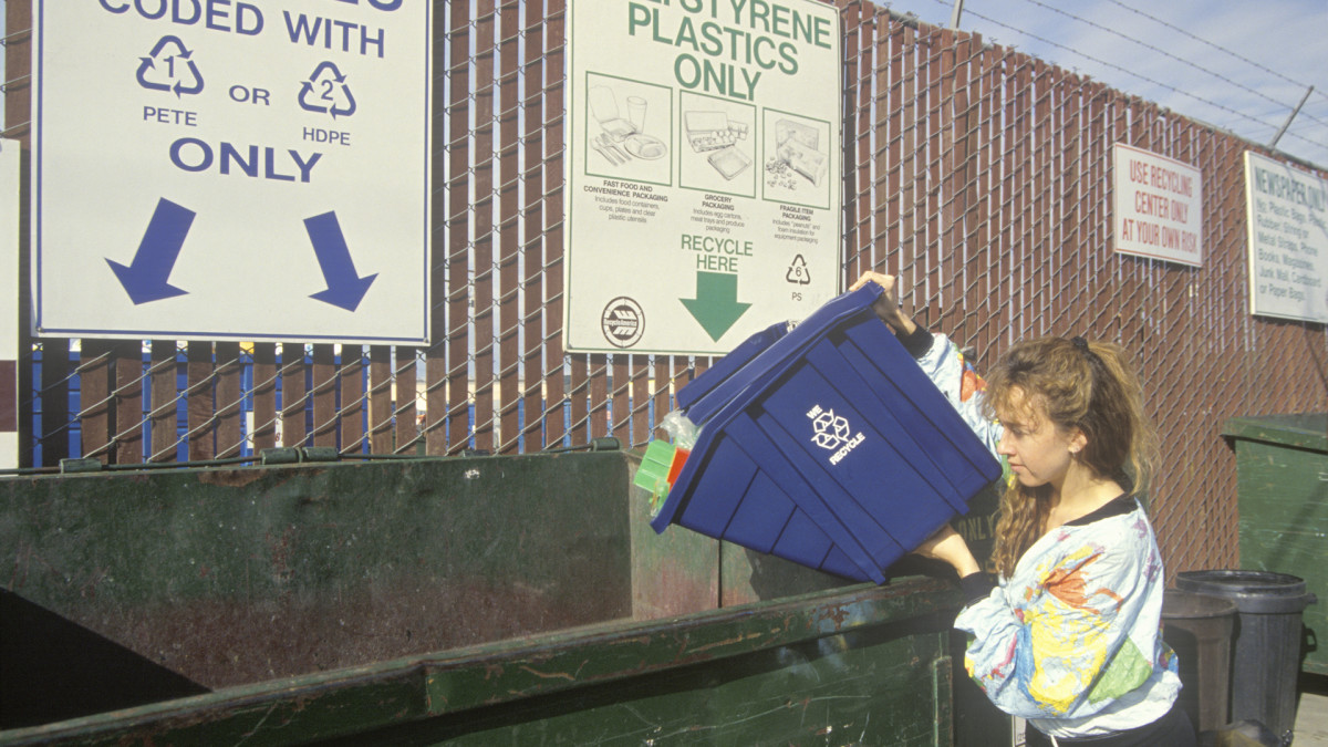 A woman recycling plastics in separate recycling containers at the Santa Monica Recycling Center, California, 1992.
