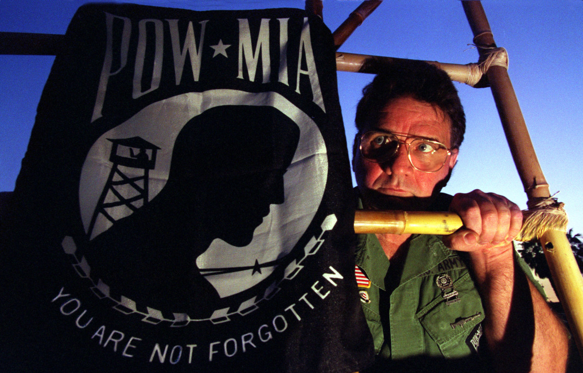Vietnam War veteran Bob Kakuk helped lead the fight to have government buildings fly the flag of prisoners of war and missing in action. Kakuk poses with the flag and a mockup of a bamboo POW cage he uses to dramatize the cause.