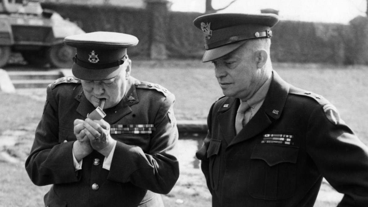British Prime Minister Winston Churchill lighting a cigar while staying at the Allied Headquarters in France with U.S. General Eisenhower, March 1945.