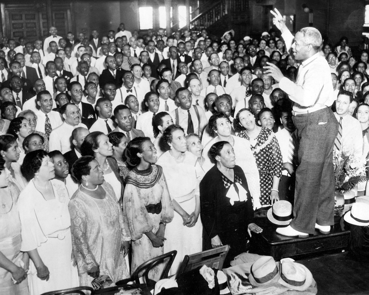 """J. Wesley Jones, choral director, leads 600 Black singers through a rehearsal in Chicago, August 1935. The group was rehearsing for the upcoming Chicagoland Music Festival where they would sing """"Swing Low, Sweet Chariot"""" at Soldier Field."""
